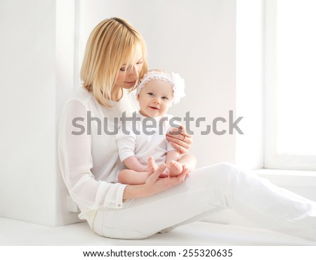 Young mother with her baby at home in light room near window