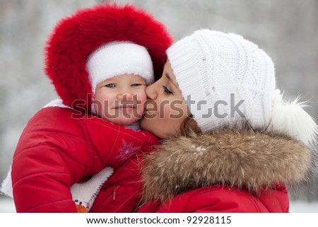 Young mother with her baby daughter in their red jackets - stock photo