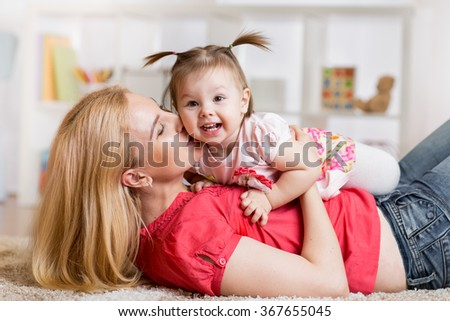 young mother with her baby having fun pastime - stock photo