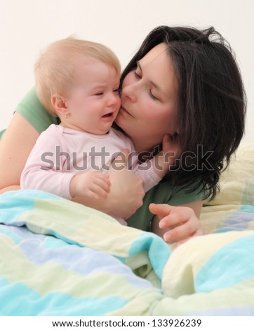 Young mother with her baby in the bed. - stock photo