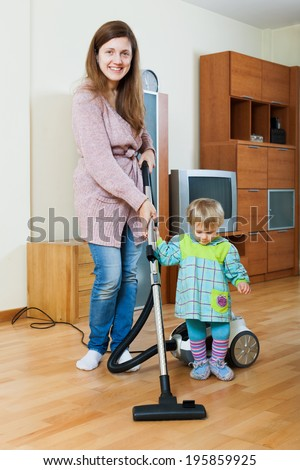 Young mother with her child doing home cleaning with a vacuum cleaner - stock photo