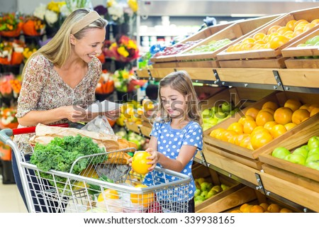 Young mother with her daughter at supermarket - stock photo