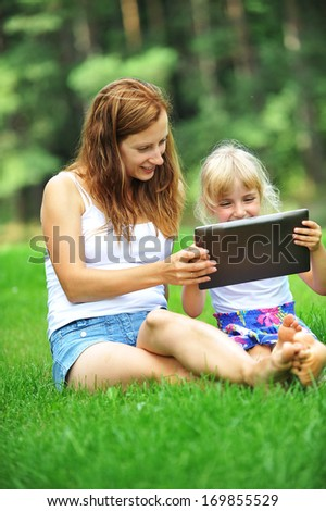 young mother with her daughter  looking at screen of laptop. summer day. - stock photo
