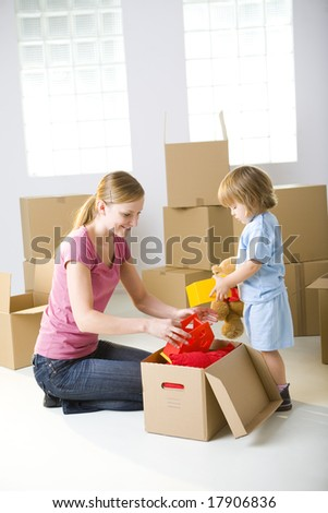 Young mother with her daughter sitting between cardboard boxes. A woman taking toy from box. Young girl holding teddy bear.