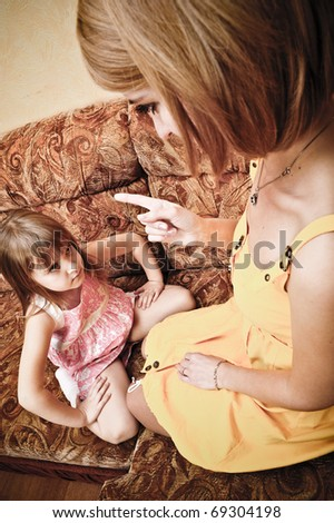 Young mother with her daughter sitting on sofa and educating - stock photo