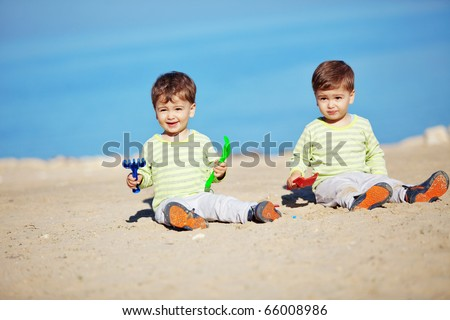 Young mother with her infant kids resting at the beach - stock photo