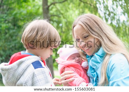 Young mother with her kids in the forest. Son is jealous mum of younger sister. - stock photo