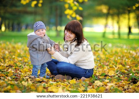 Young mother with her little baby boy having fun in the autumn park - stock photo