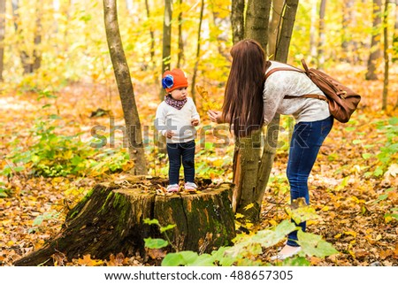 Young mother with her little baby girl in the autumn park