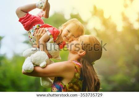 Young mother with her little baby on the meadow  - stock photo