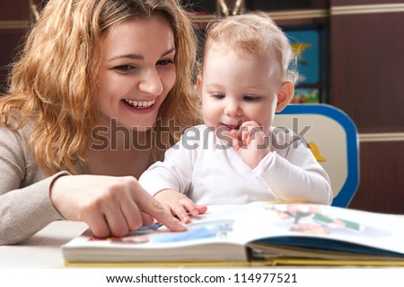 Young mother with her little daughter reading book - stock photo