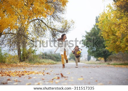 Young mother with her little daughter walking in fall park on yellow fallen leaves one autumn day - stock photo
