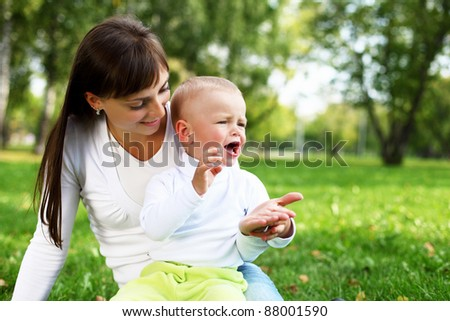 Young mother with her little son in summer park