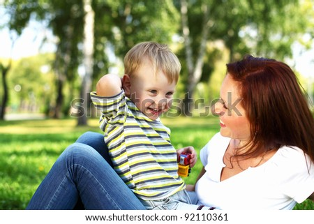 Young mother with her little son in summer park - stock photo