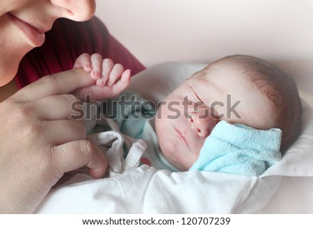 Young mother with her newborn baby boy. - stock photo
