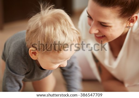 Young mother with her one years old little son dressed in pajamas are relaxing and playing in the bedroom at the weekend together, lazy morning, warm and cozy scene. Pastel colors, selective focus. - stock photo