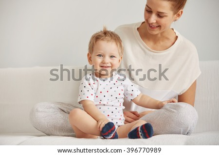 Young mother with her one years old little son dressed in pajamas are relaxing and playing in the bedroom at the weekend together, lazy morning, warm and cozy scene. Selective focus. - stock photo