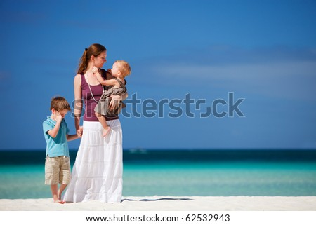 Young mother with her son and daughter on tropical beach vacation