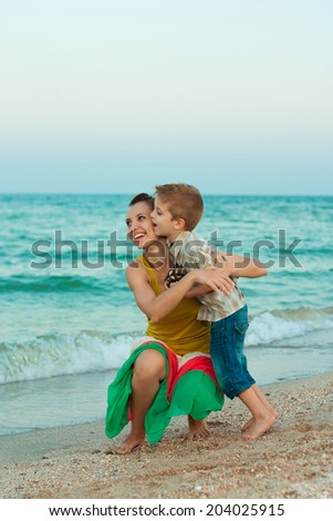 Young mother with her son having fun on the beach - stock photo