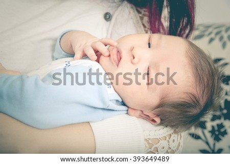 Young Mother with Her Son in Her Arms. Closeup of Sleeping Newborn Baby in Embraces of His Mum. One Month Old Baby Boy in Comfort of Moms Arms. Fall Asleep in Mother's Arms. Domestic Family at Home