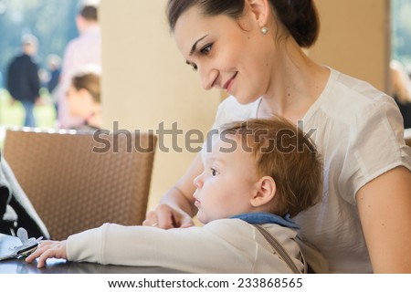 Young mother with her son in her arms.Portrait of a happy mother and baby laughing. Young mother holding her baby.Single working mom - stock photo