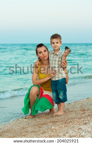 Young mother with her son on the beach with shells - stock photo