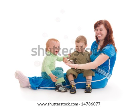 Young mother with her sons enjoy with colored soap bubbles over white background - stock photo