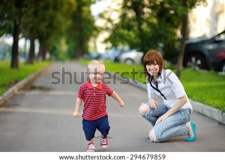 Young mother with her toddler son playing outdoors - stock photo