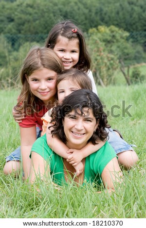 Young mother with her two daughters in a farmers field
