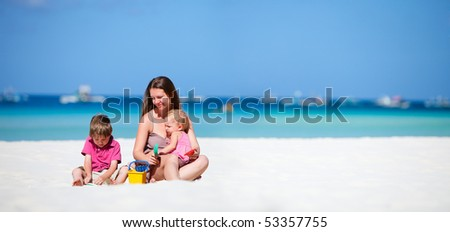 Young mother with her two kids on tropical beach vacation - stock photo