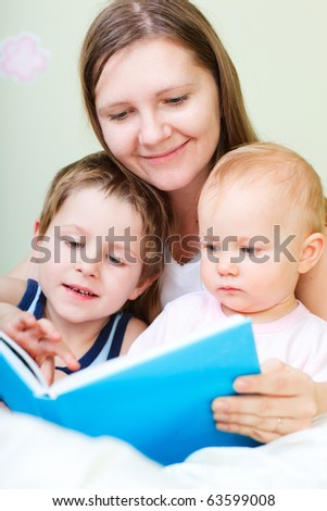 Young mother with her two kids reading book in bed
