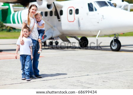 Young mother with her two kids standing in front of small airplane