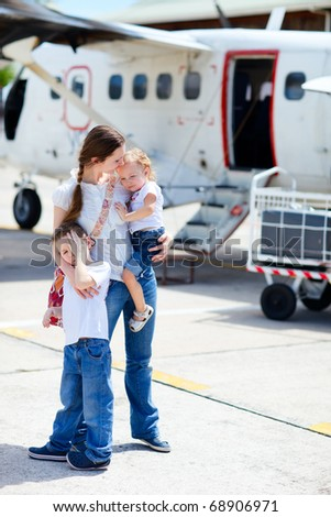 Young mother with her two kids standing in front of small airplane - stock photo