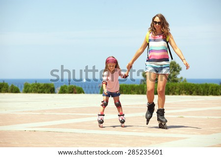 Young mother with her 5 years old daughter rollerskating in park - stock photo