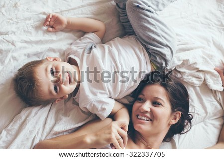 Young mother with her 2 years old son dressed in pajamas are relaxing and playing in the bed at the weekend together, lazy morning, warm and cozy scene. Pastel colors, selective focus, top view. - stock photo
