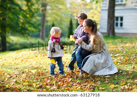 Young mother with here two kids at autumn park - stock photo