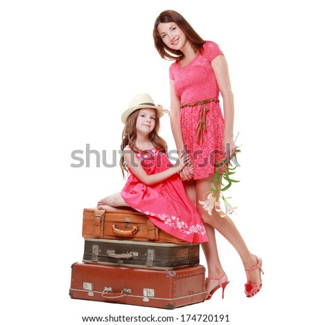 Young mother with his little daughter in a pink dress sitting on suitcases in a travel theme - stock photo