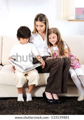 Young mother with kids reading on sofa - stock photo