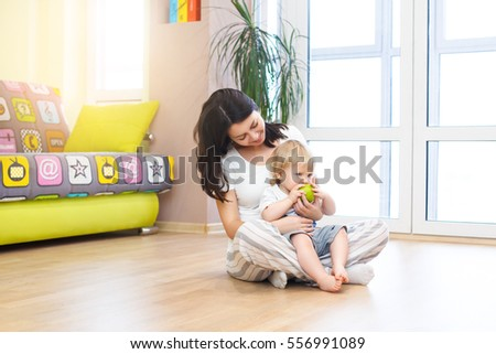 Young mother with little baby eating apple, closeup portrait, concept of health care and healthy child nutrition