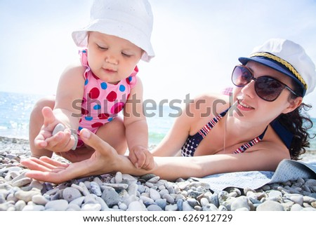 Young mother with little children playing on the beach in swimsuit