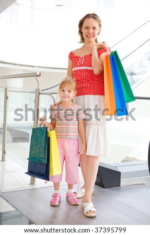 young mother with little daughter in mall with baf - stock photo