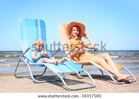 young mother with little daugther on the beach - stock photo