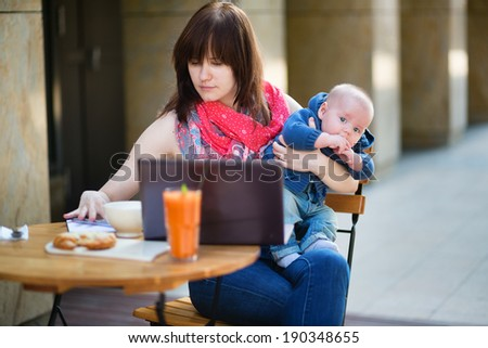 Young mother with little son working on her laptop in a cafe - stock photo