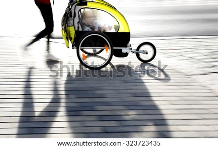 young mother with modern yellow pram walking on sidewalk