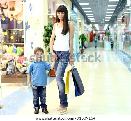 Young mother with shopping bags doing shopping - stock photo