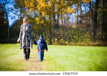 Young mother with son enjoying beautiful autumn day - stock photo