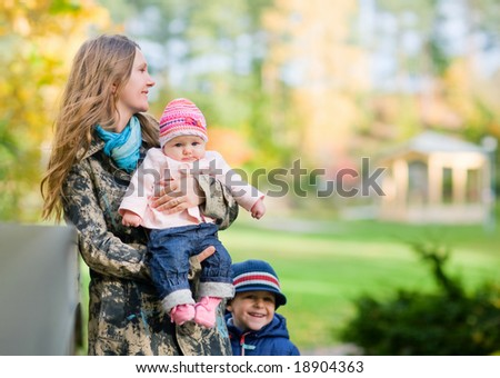Young mother with two kids enjoying beautiful autumn day