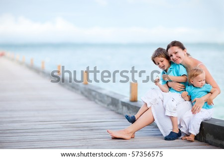 Young mother with two kids on wooden jetty by the ocean - stock photo