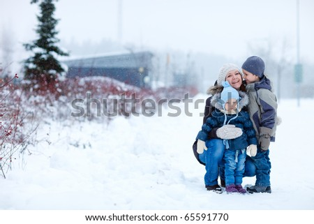 Young mother with two kids outdoors on beautiful winter day - stock photo