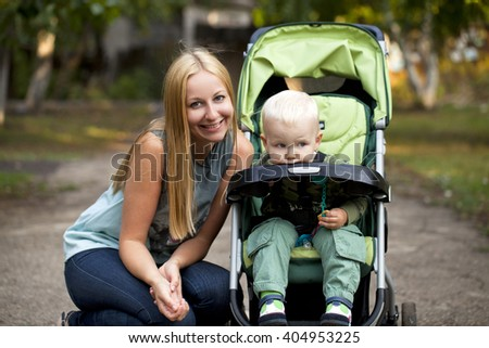 Young mother with two year old son in summer park - stock photo